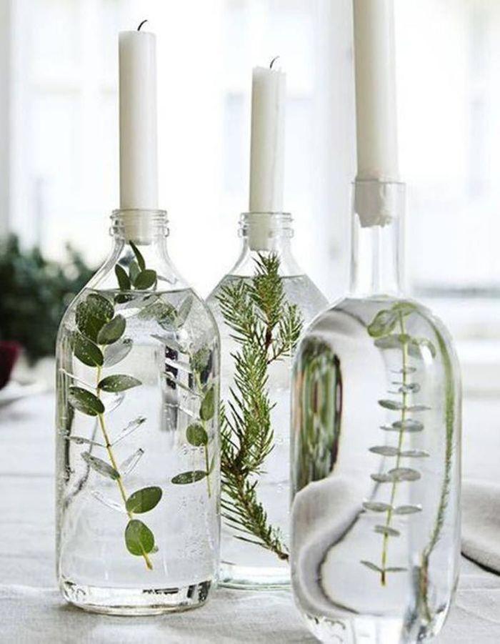 Des bouteilles en verre remplies d'eau et de feuillage pour former un chandelier végétal