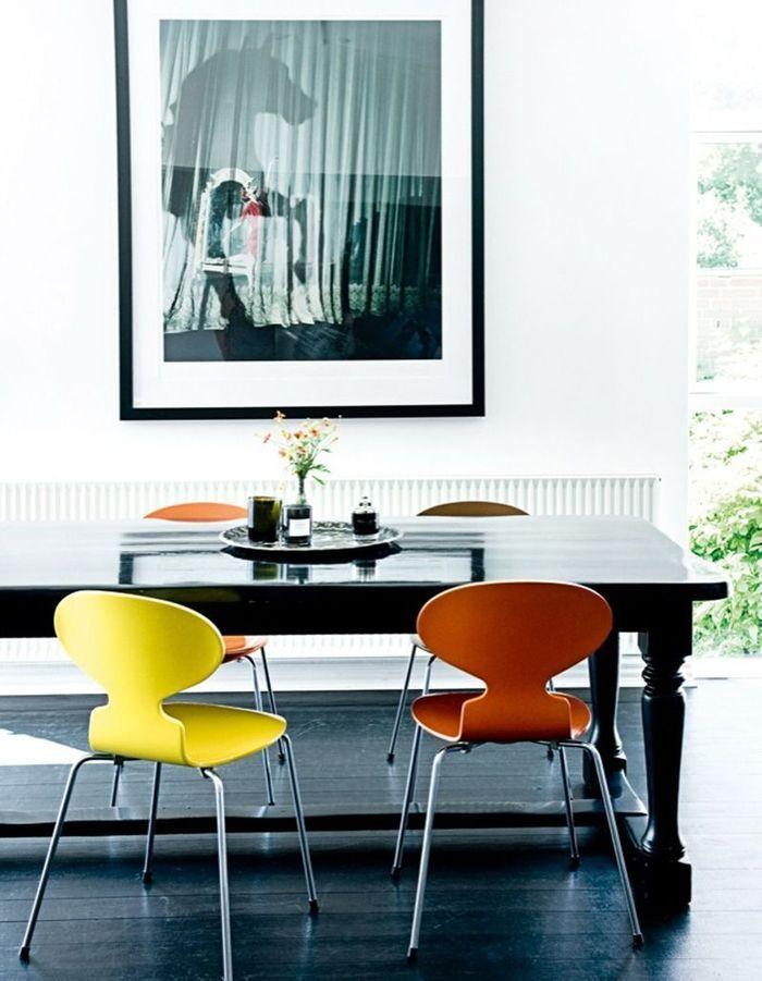 Des chaises Fourmi colorées dans une salle à manger noire et blanche