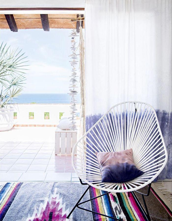 Un fauteuil Acapulco blanc mêlé à un tapis graphique