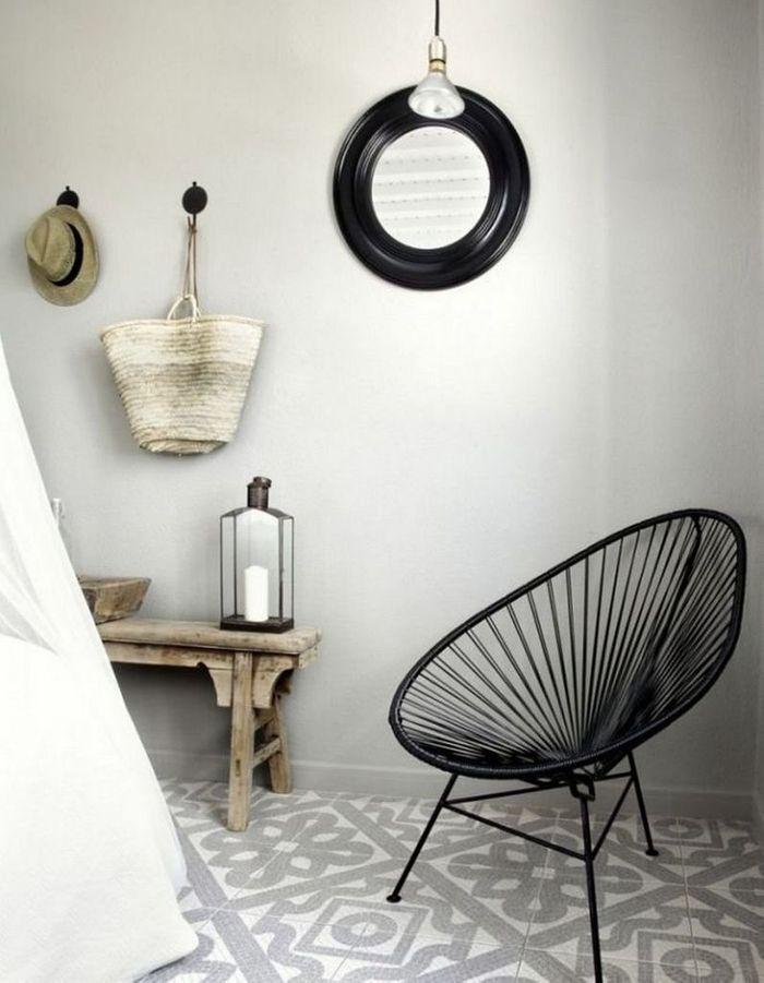 Un fauteuil Acapulco noir dans une salle de bains dépaysante
