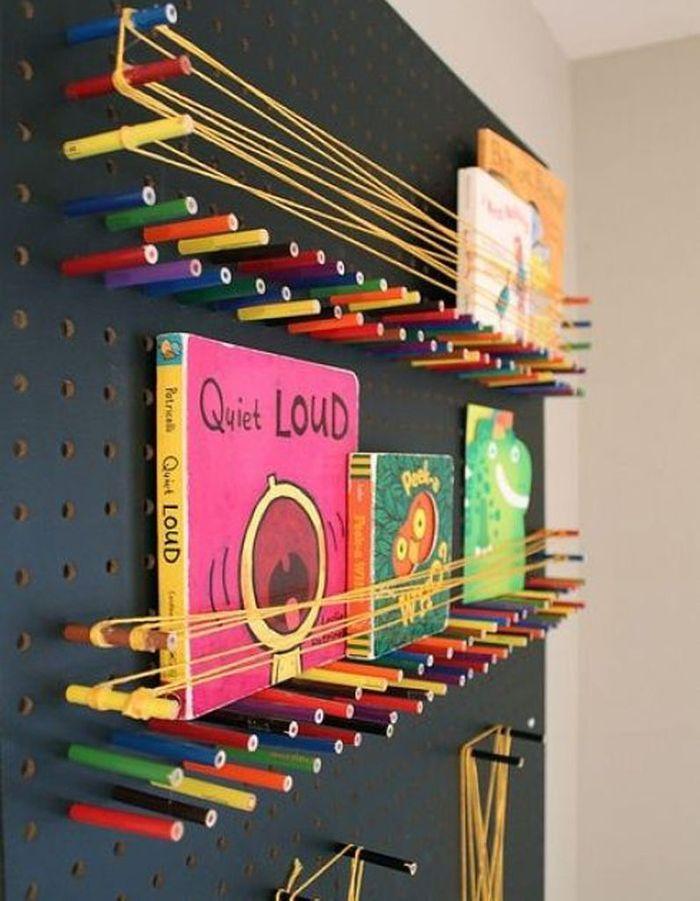 Des livres pour enfants rangés sur une structure murale, faite à partir d'une plaque perforée, de crayons de couleurs et de ficelle