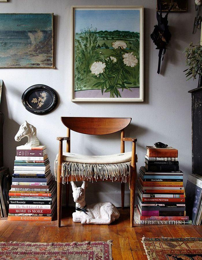Une petite bibliothèque via des piles de livres contre un mur